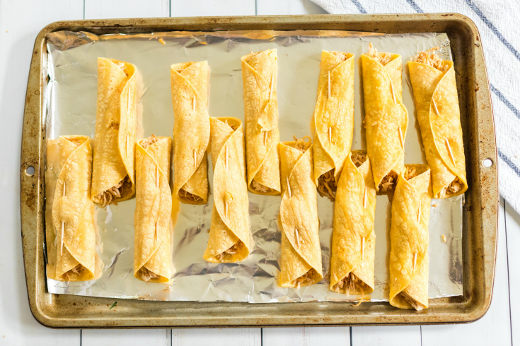Easy Chicken Taquitos - rolled up taquitos on a baking sheet