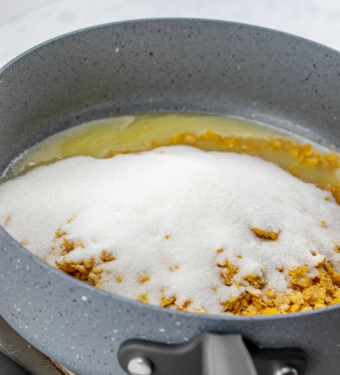 Fried Ice Cream Cake adding in sugar and corn flakes to melted butter in pan