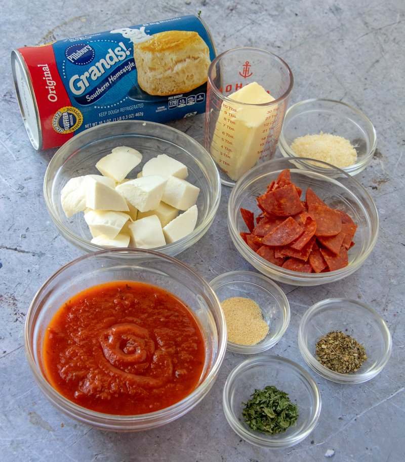 Cheesy Pizza Bombs - ingredients on counter - biscuits, cheese, butter, pepperoni, seasoning, marinara sauce.