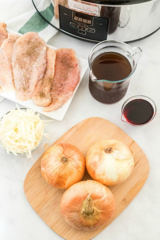 Crockpot French Onion Chicken - ingredients on table - chicken breasts, broth, wine, onions and shredded cheese