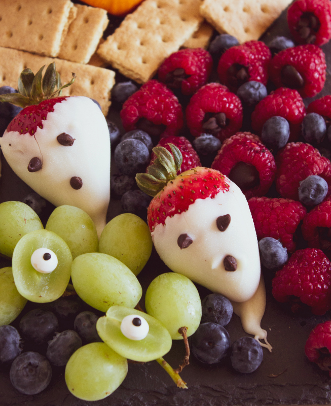Halloween Appetizer Snack Board Idea - chocolate covered strawberries, grape eyes, raspberries and blueberries