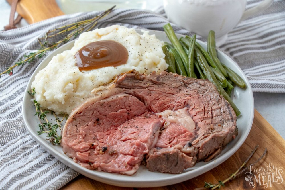 The Best Prime Rib - sliced prime rib on a plate with mashed potatoes and green beans