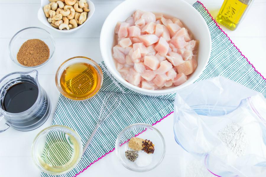 Crockpot Cashew Chicken - Ingredients in mixing bowls. Chicken, flour, seasoning, honey, brown sugar, soy sauce, oil