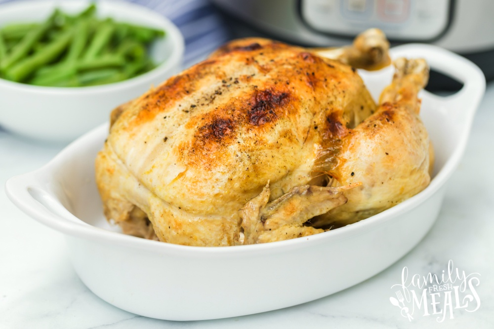 Instant Pot Dill Pickle Chicken Recipe - Cooked whole chicken in white baking dish