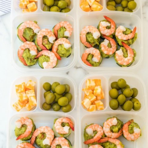 Top down photo of 4 easy lunchboxes with Shrimp Avocado, guacamole, olives and cheese cubes