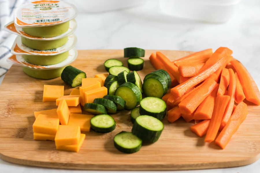 lunchbox ingredients on a cutting board - cheese, guacamole, cucumbers and carrots