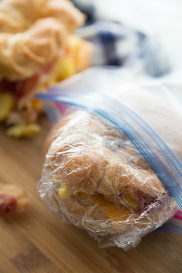 Freezer Friendly Breakfast Croissant Sandwiches - sandwiches wrapped in cling wrap and going in a ziplock bag