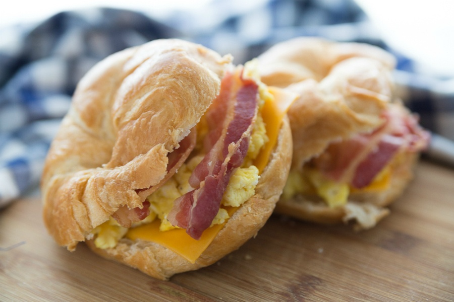 Freezer Friendly Breakfast Croissant Sandwiches - two bacon egg and cheese breakfast sandwiches on a cutting board