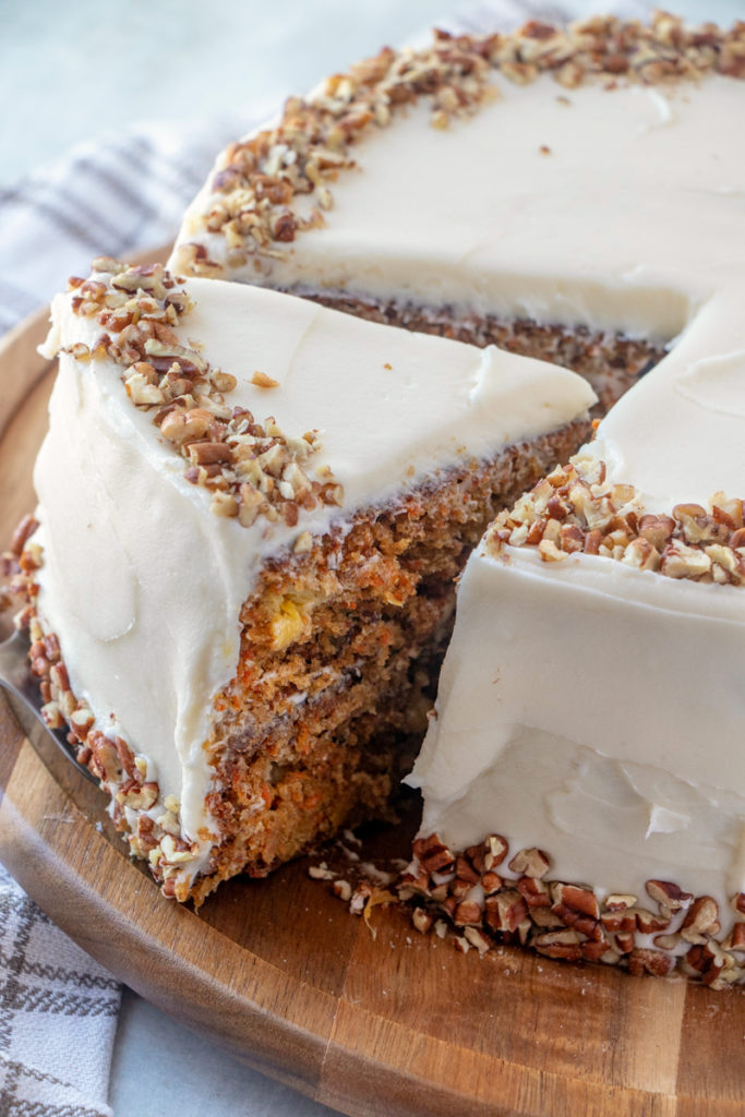 The Best Carrot Cake Recipe - cutting a slice of cake out of cake