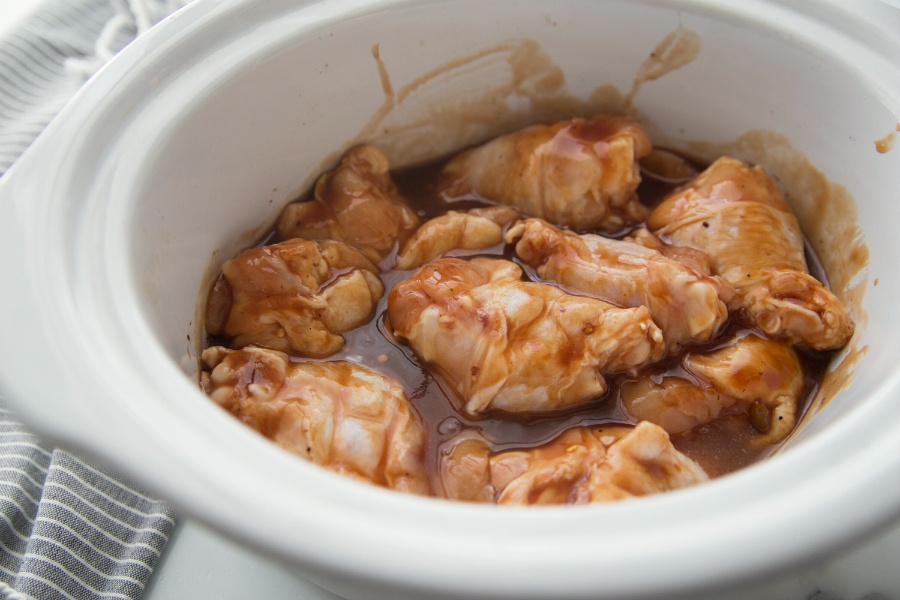 Raw chicken wings in a white crockpot and sauce
