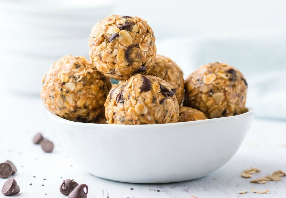 Side photo of Energy bites in a white bowl, surrounded by chocolate chips, and oat pieces