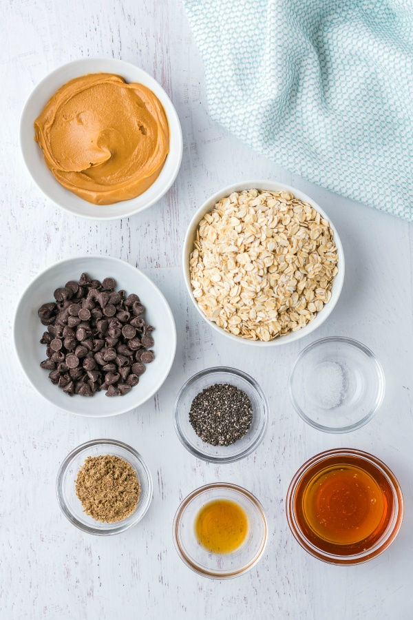 Ingredients in bowls - chocolate chips, oats, chia seeds, sugar, honey, vanilla, peanut butter and salt