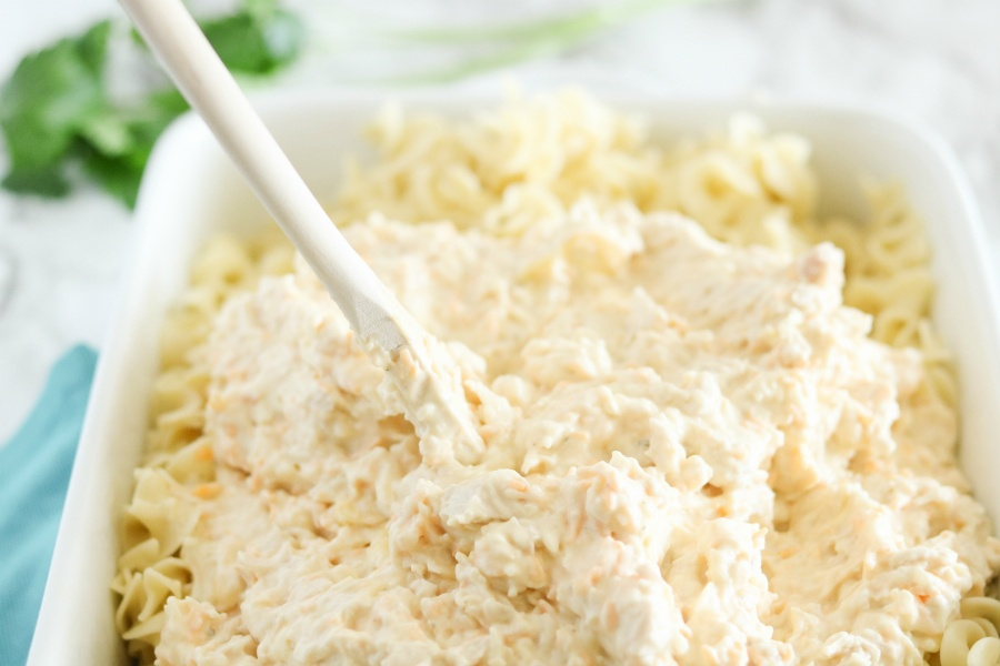 Creamy chicken mixture being placed over cooked noodles in a casserole dish