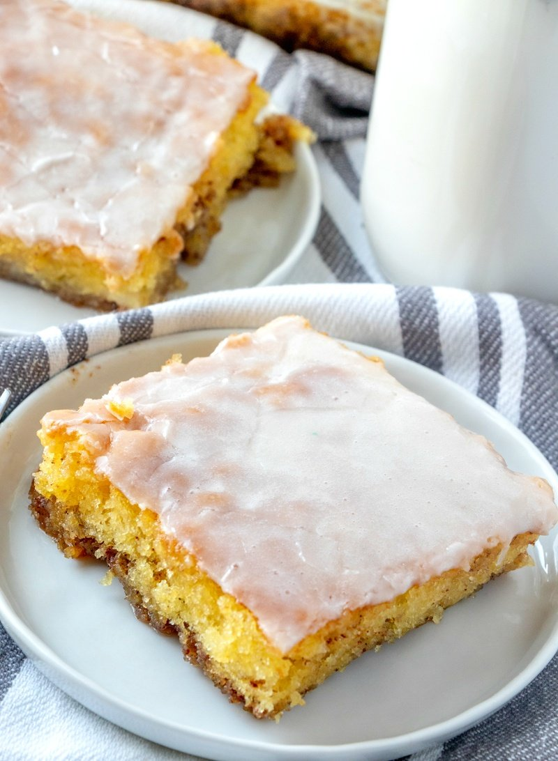 Honey Bun Cake Recipe - 2 plates with a Slice of cake on a white plate with a container of milk on the right