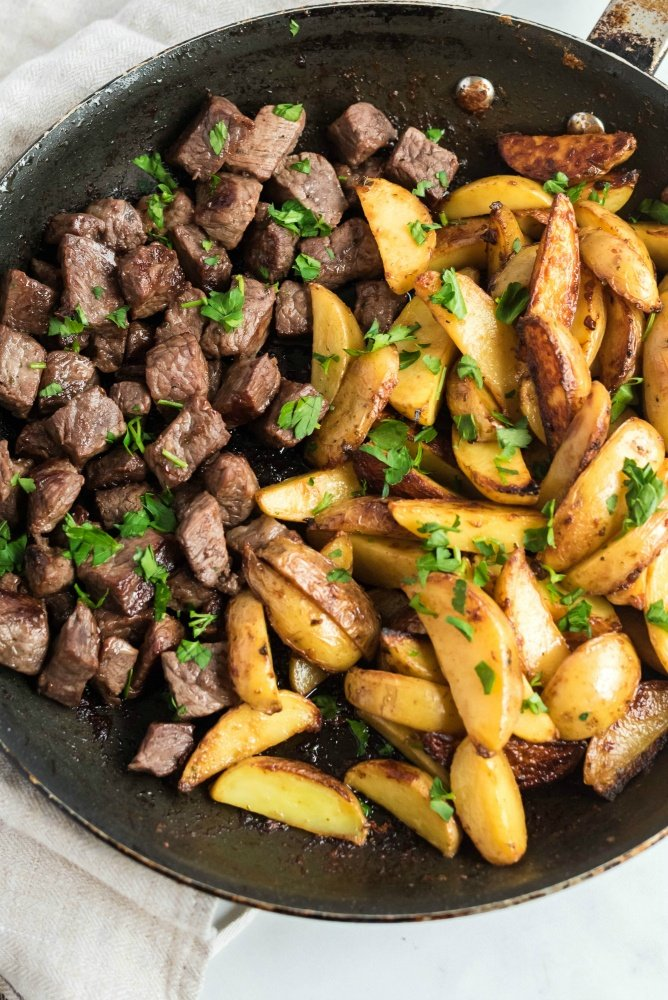 One Pot Steak and Potato Bites in a frying pan and topped with parsley