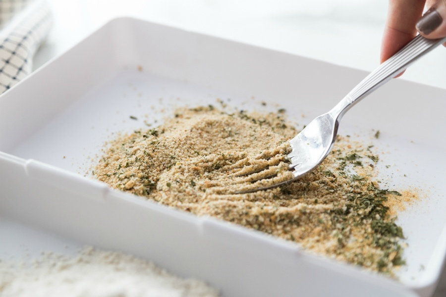 mixing together parmesan cheese, seasoning and bread crumbs with a fork
