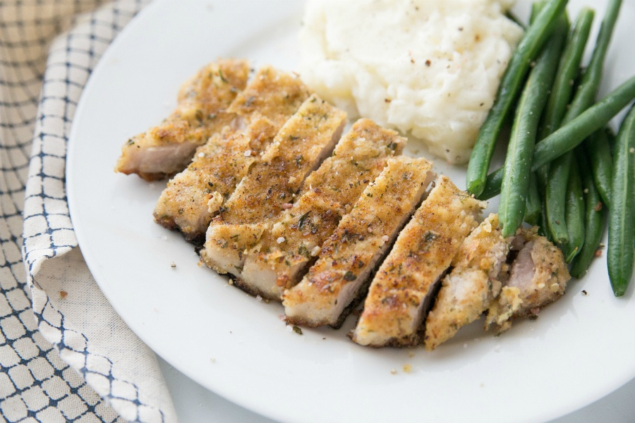 parmesan crusted pork chop, sliced, on a white plate with green beans and mashed potatoes