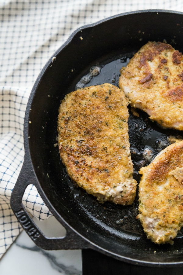 parmesan crusted pork chops cooking in a cast iron pan