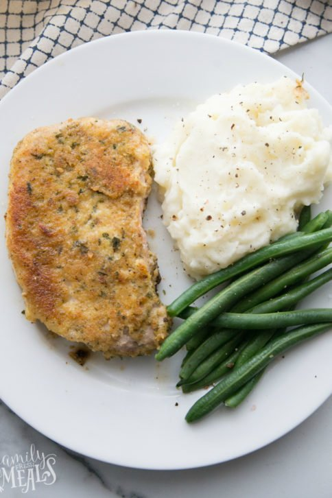 Top down picture of parmesan crusted pork chop on a white plate with green beans and mashed potatoes