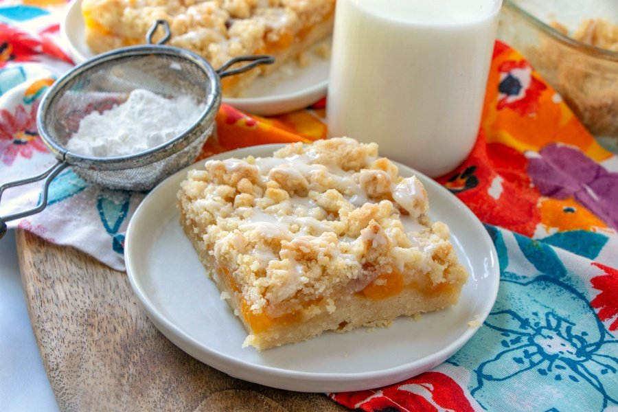 piece of peach crumble bar on a white plate with jug of milk in background and sugar sifter sitting left of the plate