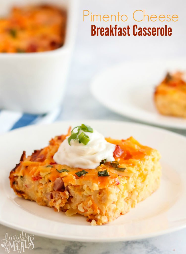 Pimento Cheese Breakfast Casserole - a piece of breakfast casserole on a white plate, topped with a dolip of sour cream and sliced green onions - words on the upper right saying pimento cheese breakfast casserole.jpg