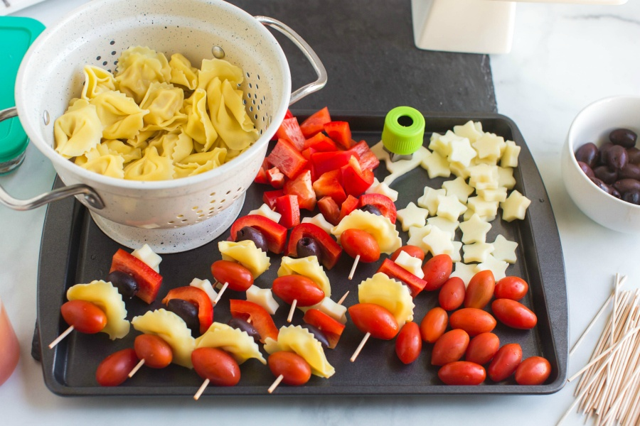 pasta, olives and cheese stars on a baking sheet, being made into kabobs