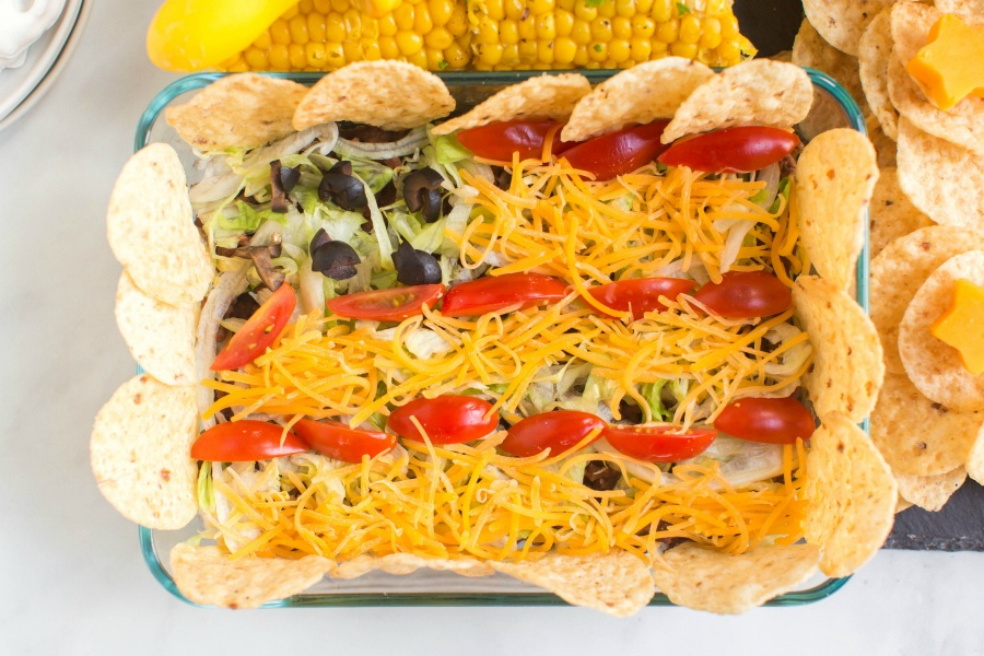 small taco salad with shredded cheese, tomatoes, lettuce, and chips, laid out to look like an American Flag, set on the 4th of July Snack Board