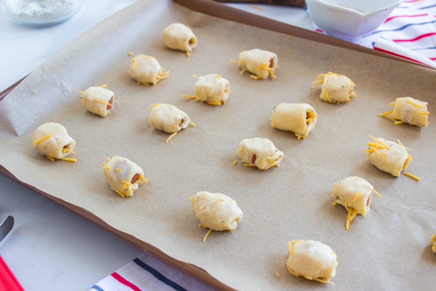 Hotdog pieces wrapped in cheesy dough on a parchment paper lined baking sheet