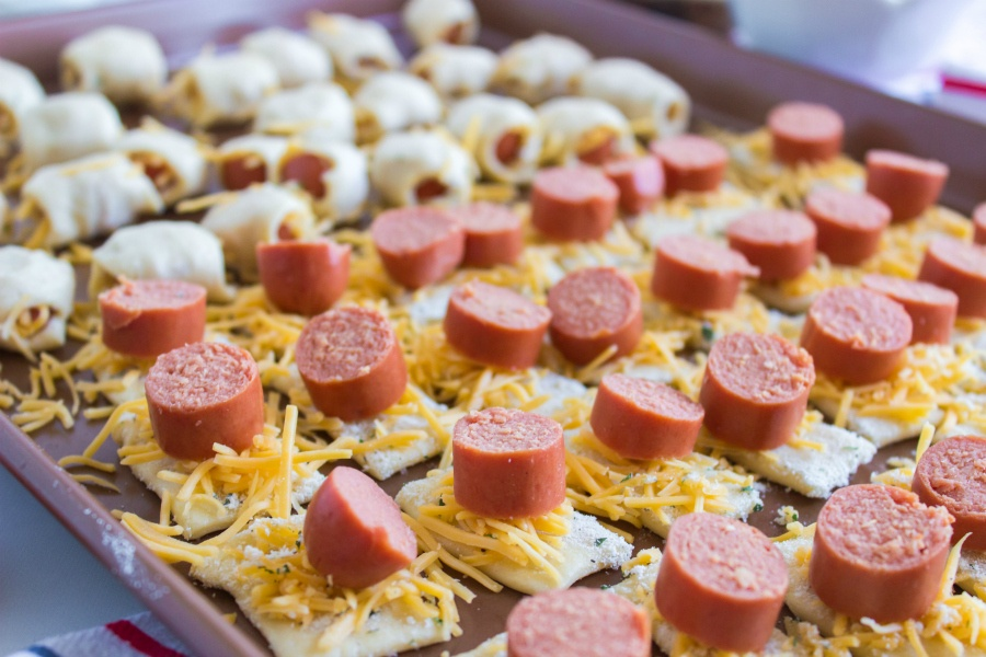shredded cheese and hot dog pieces on top of crescent dough pieces