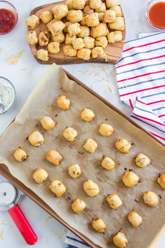 top down image of baked hotdog pieces wrapped in cheesy dough on a parchment paper lined baking sheet and also a pile of hotdog nuggets on a platter