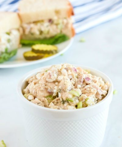Cottage Cheese Tuna Salad in a small white bowl, with a sandwich in the background