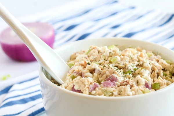 Cottage cheese tuna salad in a white bowl with a mixing spoon