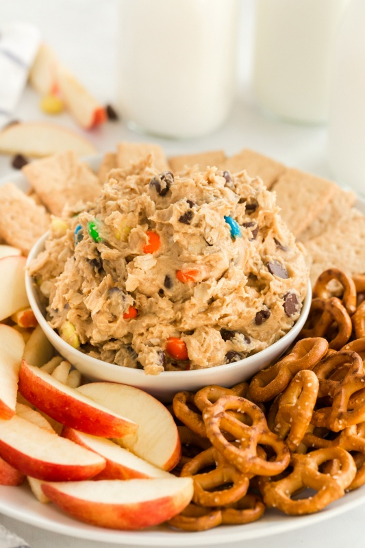 Monster Cookie Dough Dip served in a white bowl, surrounded by pretzels, sliced apples and graham crackers. With glasses of milk in the background