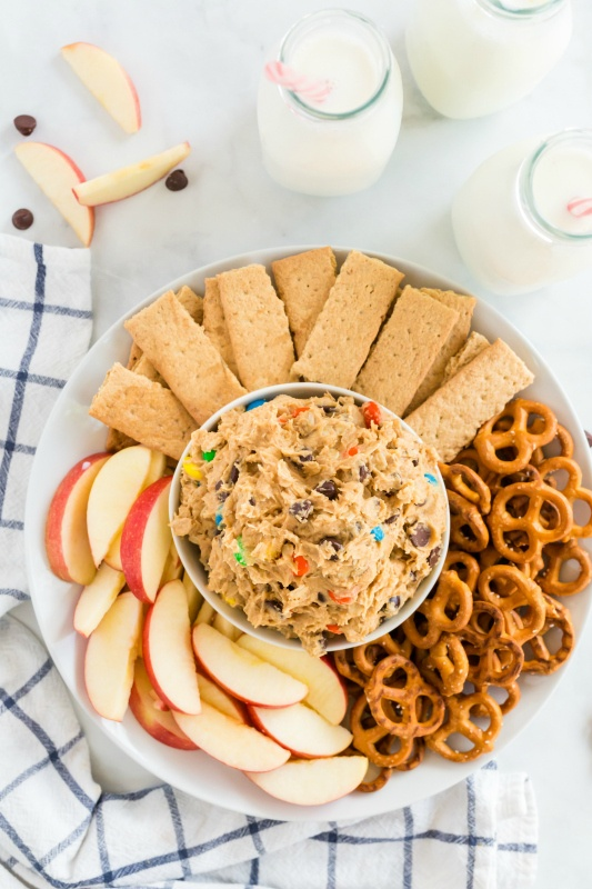 Monster Cookie Dough Dip served in a white bowl, surrounded by pretzels, sliced apples and graham crackers.