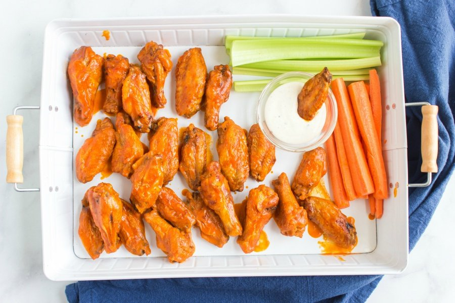 Buffalo chicken wings served on a platter with ranch dressing, carrots and celery