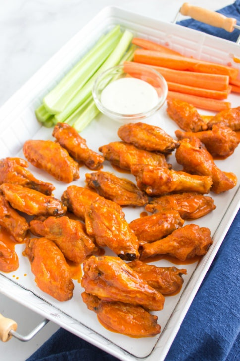 buffalo wings, celery and carrot sticks on a serving platter, with s dipping cup of dressing