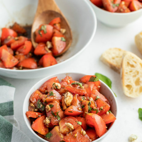 Balsamic Tomato Salad recipe served in a two small white bowl with a side of french bread