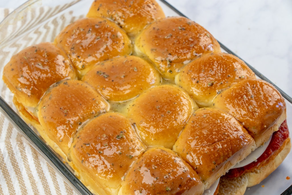 sliders in a baking sheet with butter mixture brushed on top