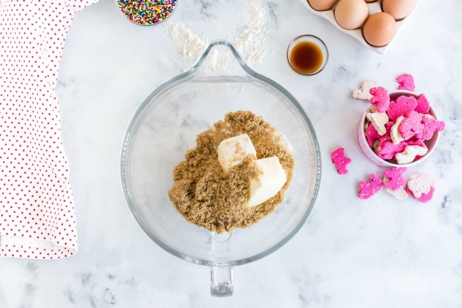 Sugars and butter in mixing bowl with a side bowls of animal cookies, vanilla, sprinkles and eggs in carton