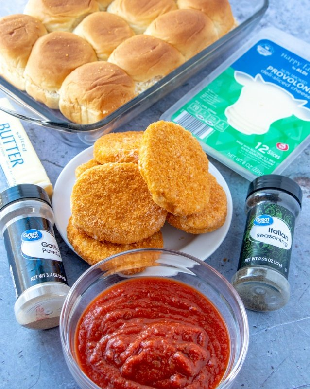 picture of ingredients for slides. Seasons containers, bowl of red sauce, plate of breaded chicken patties, package of sliced cheese and slider rolls in a baking pan