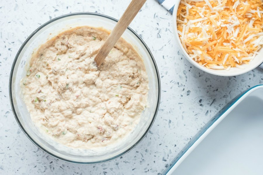 Creamy mixture in a glass mixing bow and a small bowl of shredded cheese