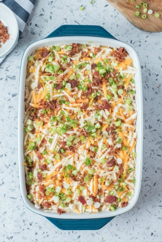Shredded cheese, bacon and chives on top of chicken lasagna