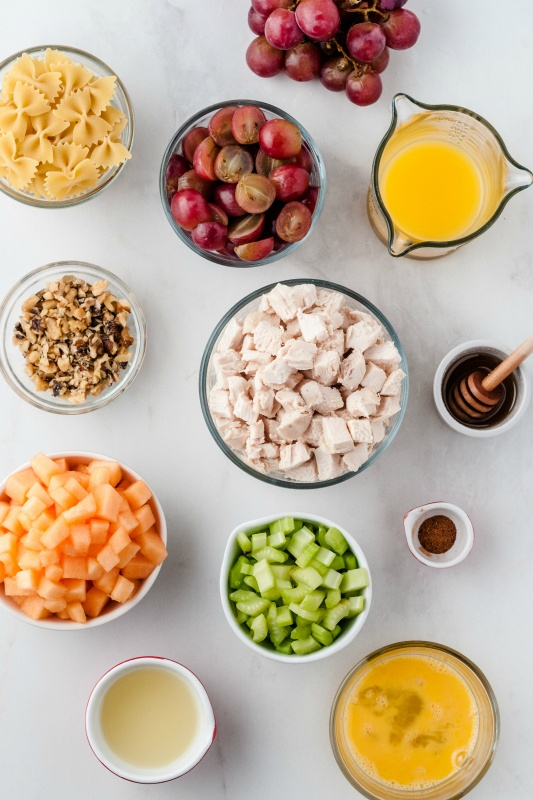 Fresh Fruity Chicken Pasta Salad - Ingredients in glass bowls - bow tie pasta, grapes, orange juice, beaten eggs, honey, nutmeg, cubed cantaloupe, cooked cubed chicken, sliced celery, lemon juice, and chopped walnuts