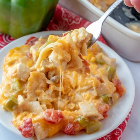 King Ranch Chicken Casserole served on a white plate with a fork scooping up a bite