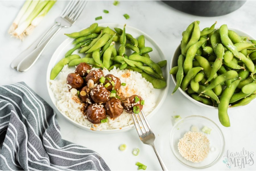 Teriyaki Meatballs served over rice on a white plate, with a side of edamame