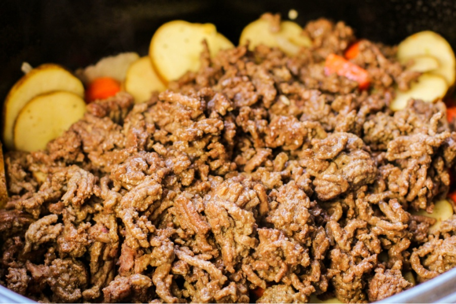 cooked ground beef being add to crockpot