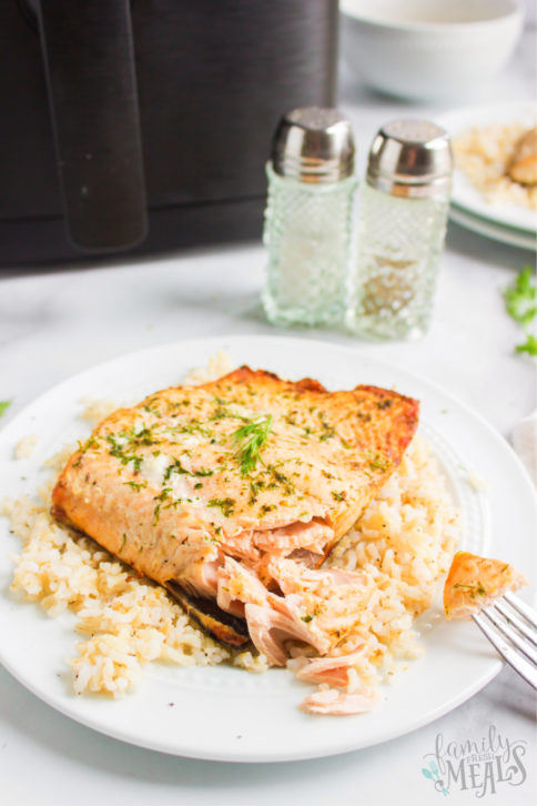 piece of air fryer salmon on a bed of rice - served on a white plate