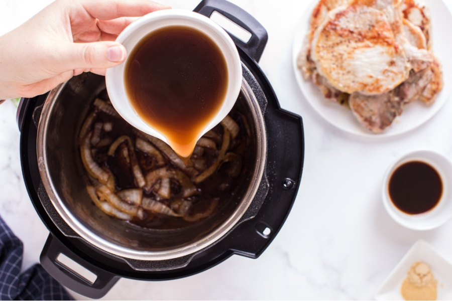 pouring broth into instant pot with onions
