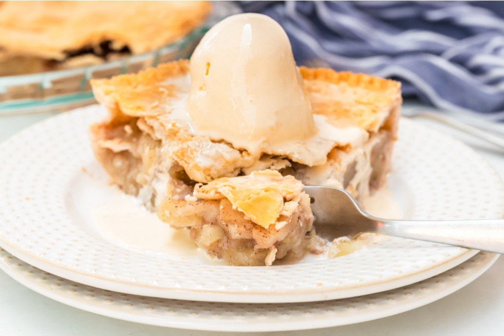 slice of apple pie on a plate with a scoop of ice cream on top and a fork cutting off a piece