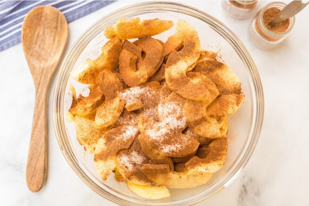 apple slices in a bowl topped with cinnamon and sugar